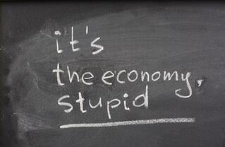 Blackboard displaying the words, 'it's the economy, stupid' in white chalk
